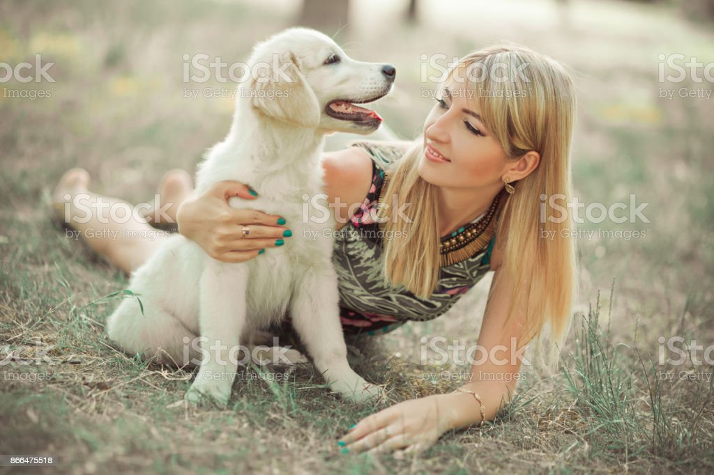Retriever pup Lovely scene beautifull blond lady woman enjoy posing summer time vacation with best friend dog ivory white labrador puppy.Happy airily careless life world of dreams with puppies. stock photo