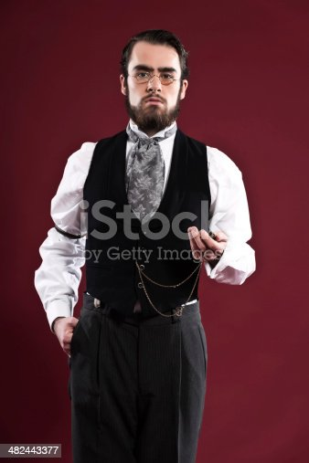 Retro 1900 victorian fashion man with beard wearing black gilet grey tie and glasses. Holding pocket watch. Studio shot against red wall.