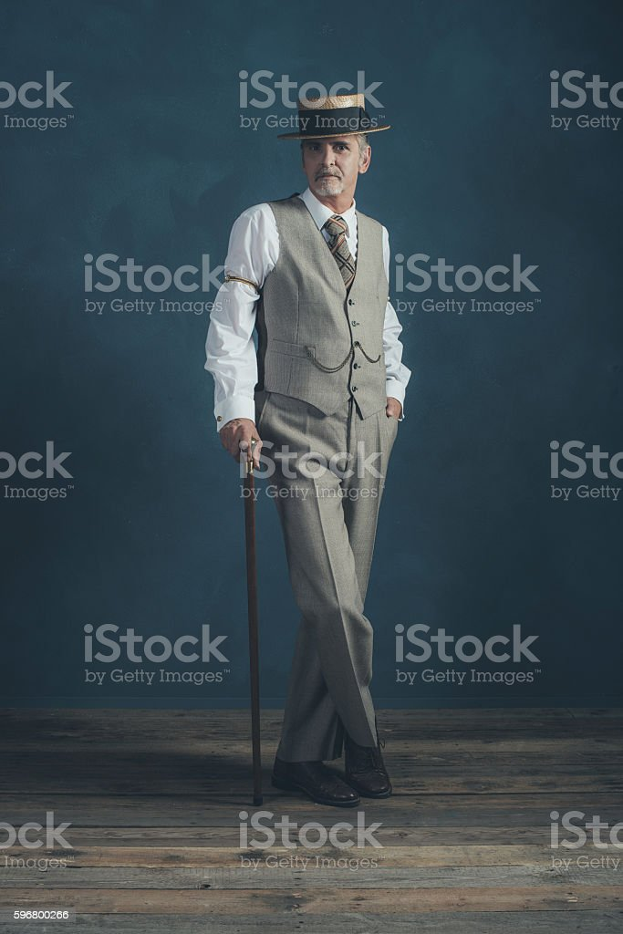 Retro 1920s dandy in suit standing with cane. - foto de stock