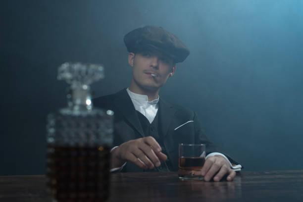 retro 1920s english gangster sitting at table with whiskey. - schiebermütze stock-fotos und bilder