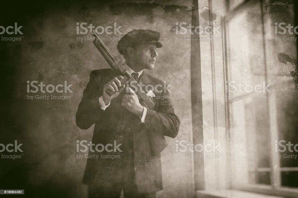 Retro 1920s english gangster wearing flat cap and suit. Standing with gun looking out window. stock photo