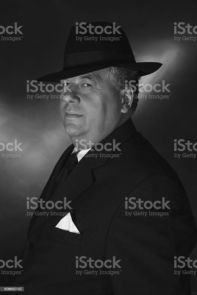 Retro 1930s gangster wearing hat. Classic black adn white portrait. stock photo