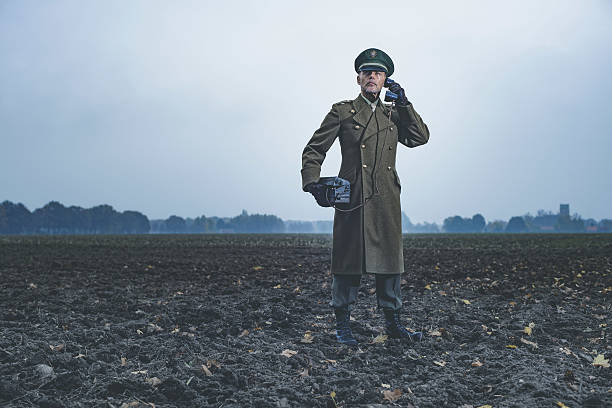 Retro 1940s military officer calling with field phone on farmland. - foto de acervo