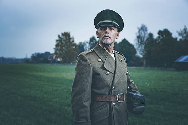 Retro 1940s military officer standing in field with phone. - foto de acervo