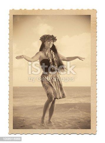 A retro old vintage style photo postcard look of a beautiful Hawaiian Hula dancer dancing on the beach of the tropical Hawaiian islands. Photographed in horizontal format with copy space in Kauai, Hawaii.