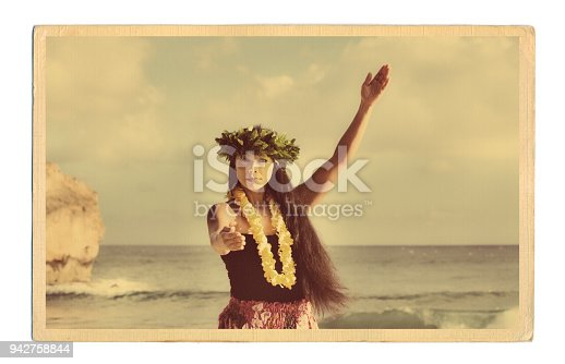 A retro old vintage style photo postcard look of a beautiful Hawaiian Hula dancer dancing on the beach of the tropical Hawaiian islands. Photographed in horizontal format with copy space in Kauai, Hawaii.