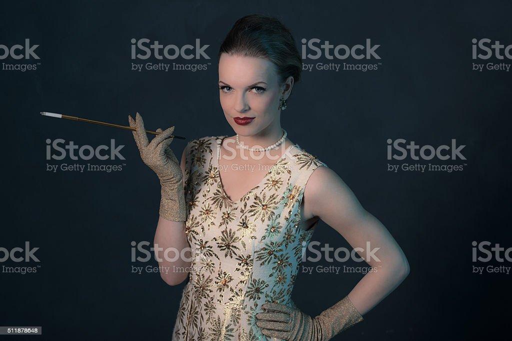 Retro 1950s posh fashion woman in gold dress holding cigarette. stock photo