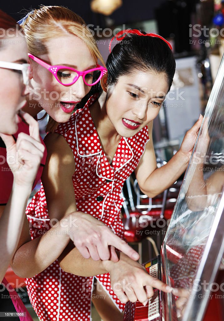 Retro 1950's Young Ladies Choosing Music From Jukebox stock photo