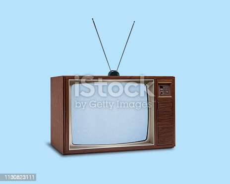 A retro 1970's television with rabbit ears on top on a blue background.Static appears on the screen.