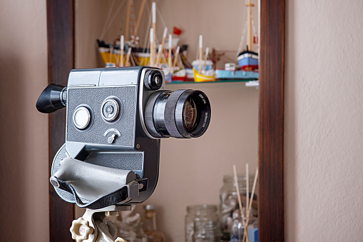Home decor object concept: Vintage 35mm. movie camera in front miniature ship models.