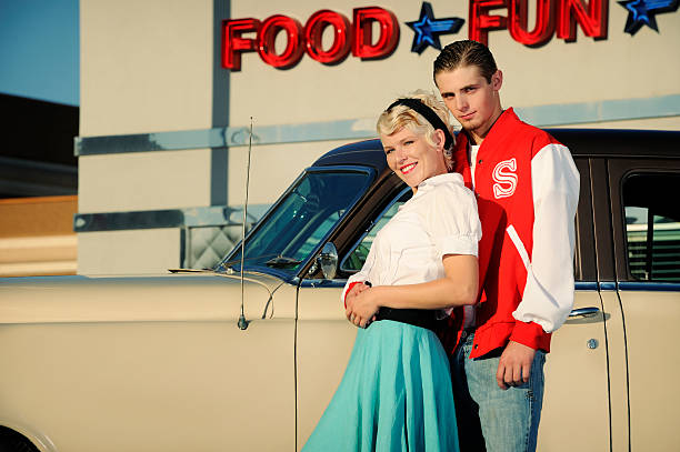 Retro 50's Couple Standing Near Old Car And Diner stock photo