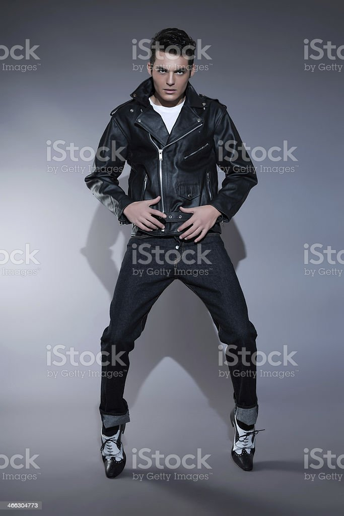 Retro 50s fashion man wearing black leather jacket and jeans. stock photo