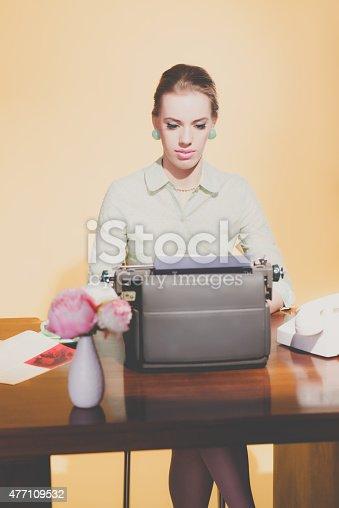 istock Retro 50s young blonde secretary woman sitting behind desk worki 477109532