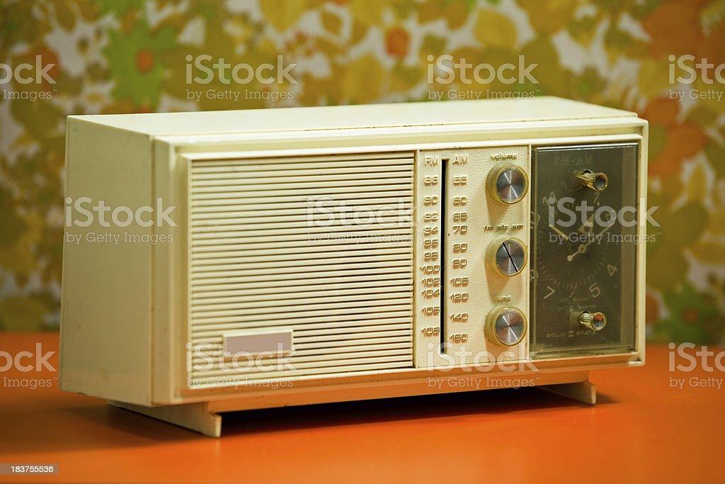 Retro 60's 70's Clock Radio with floral wallpaper background orange stock photo