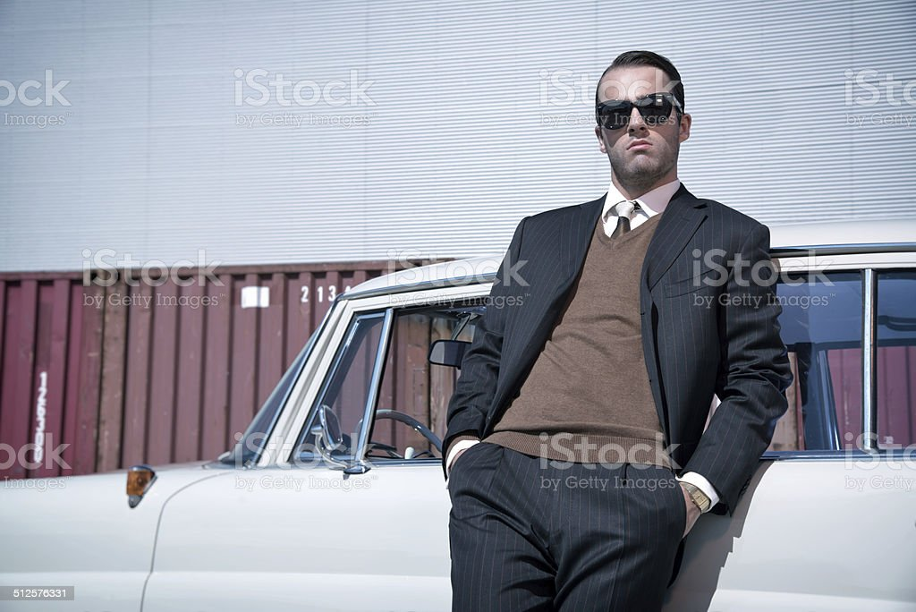 Retro 60s fashion business man wearing grey suit and sunglasses. stock photo