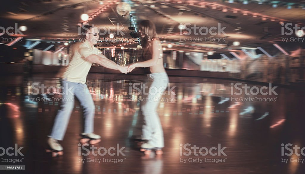 Retro 70's Roller Disco Couple in Blurred Motion stock photo