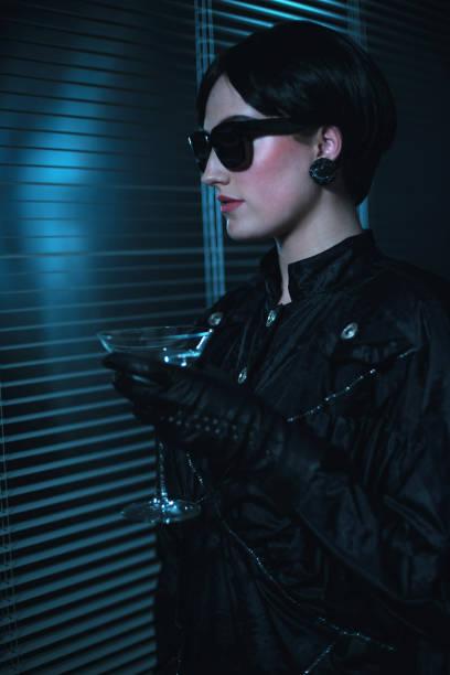 rétro années 80 femme noirs lunettes de soleil et robe tenant le verre à cocktail. - cosmetique store photos et images de collection