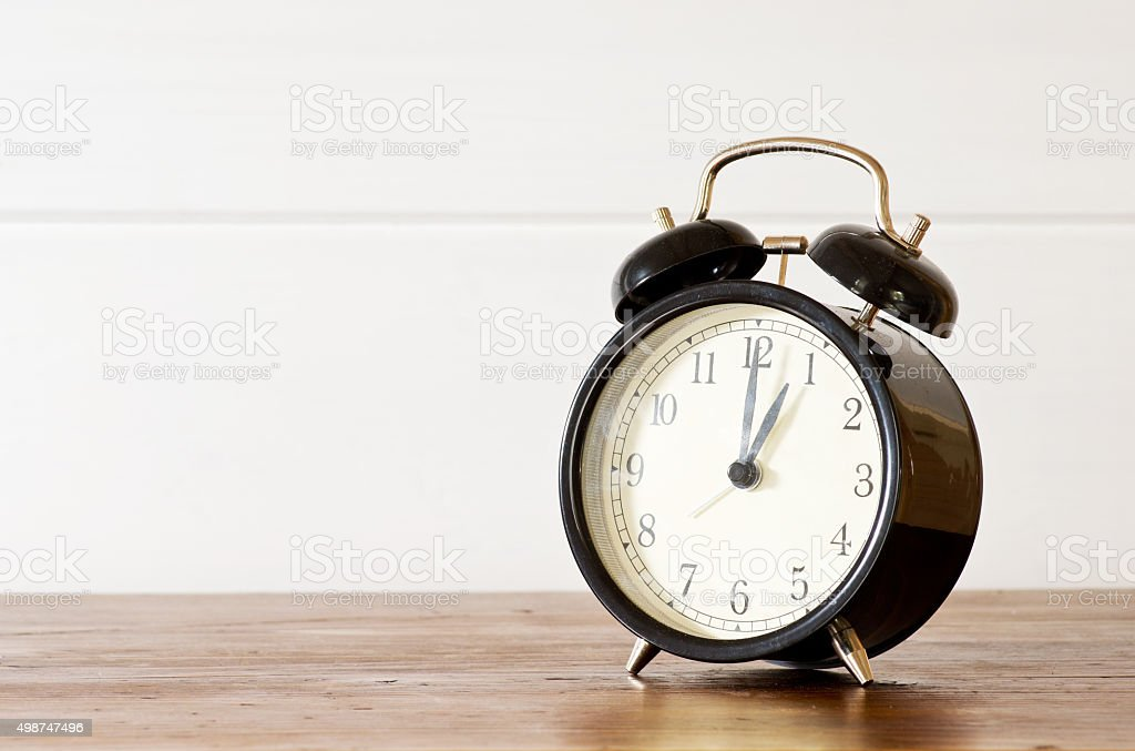 Retro alarm clock and white wooden wall background stock photo