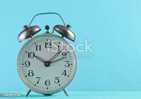 istock Retro alarm clock closeup on a blue background. 1161421176
