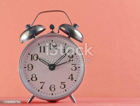 istock Retro alarm clock closeup on pink background. 1206889764