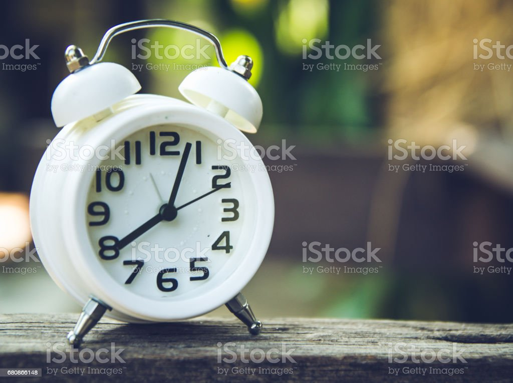 Retro alarm clock on a table. Photo in retro color image style royalty-free stock photo