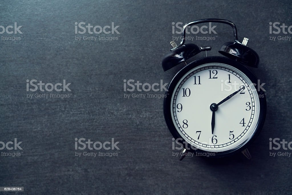 Retro alarm clock on black background stock photo