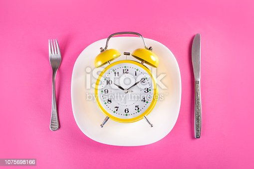 istock Retro alarm clock on plate with fork and knife. Chrono diet concept 1075698166