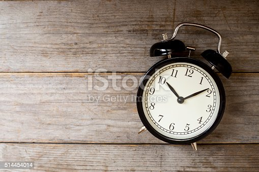 istock Retro alarm clock on wooden table 514454014
