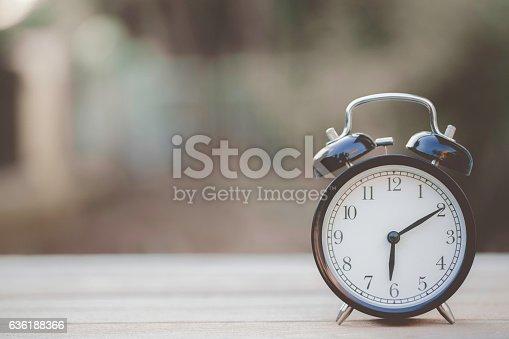 istock Retro alarm clock on wooden table, vintage style 636188366