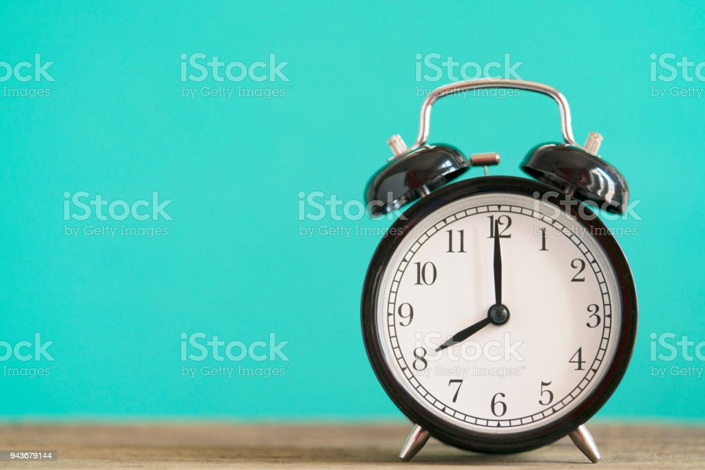 Retro alarm clock on wooden table with green background, vintage style stock photo