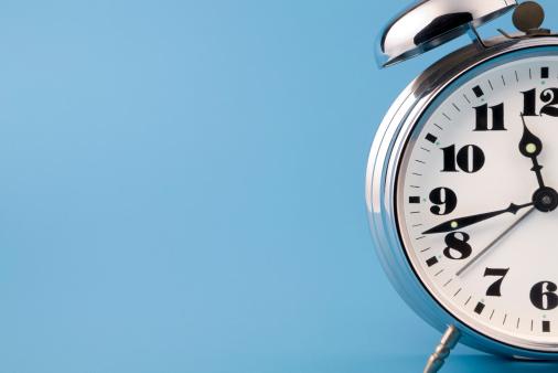 Retro chrome alarm clock detail on blue background. No sharpering.