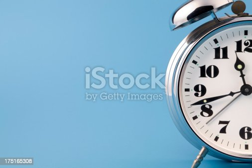 Retro chrome alarm clock detail on blue background. No sharpering.
