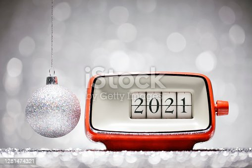 Retro alarm clock showing the number 2021. A Christmas ornament hanging besides it. White defocused lights in the background.