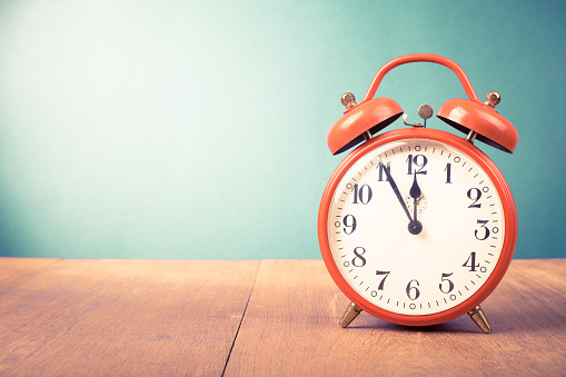 istock Retro alarm clock with five minutes to twelve o'clock. Old style filtered photo 1048902046