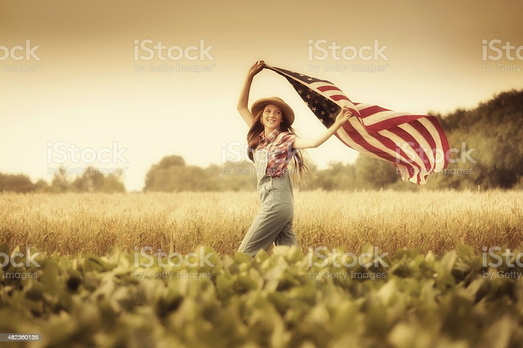 Retro Americana Girl Waving U.S.A. Flag on Fourth of July stock photo