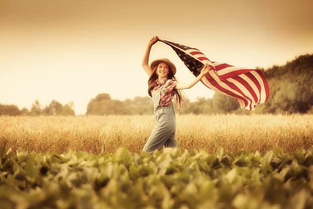 Retro Americana Girl Waving U.S.A. Flag on Fourth of July stock photo