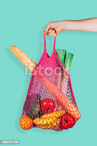 Woman hand holding a fuchsia string shopping bag with vegetables, fruits and bread in front of a green mint background