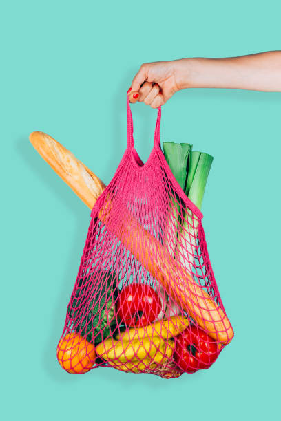 Retro and ecological string shopping bag in woman hand Woman hand holding a fuchsia string shopping bag with vegetables, fruits and bread in front of a green mint background netting stock pictures, royalty-free photos & images