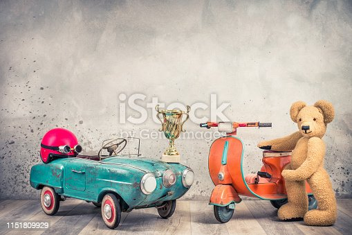 istock Retro antique aquamarine rusty pedal car from 60s, red helmet with goggles, race winner golden cup, old orange children's scooter and Teddy Bear plush toy front loft wall. Vintage style filtered photo 1151809929