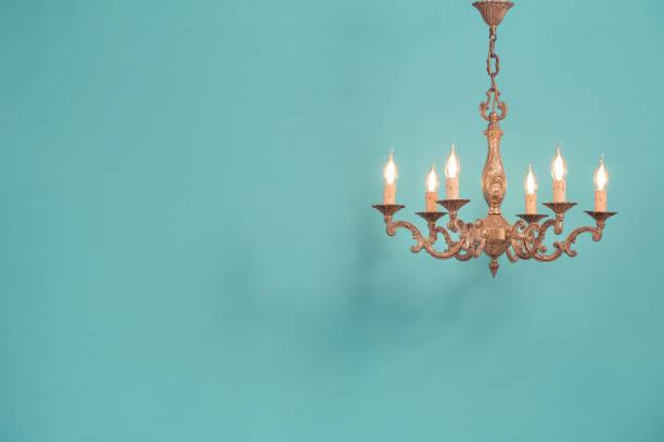 Retro antike alte Bronze Kronleuchter mit Glühbirnen geformtkerzen hängen vor mint blau Wandhintergrund. Nostalgie-Beleuchtungskonzept. Vintage-Stil gefiltertfoto – Foto