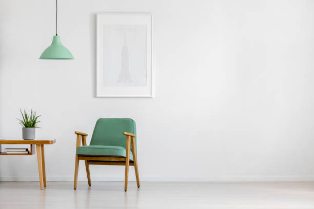 Retro armchair in bright interior Retro concept mint pastel armchair, wooden table and framed poster in a bright minimalist interior with copy space armchair stock pictures, royalty-free photos & images