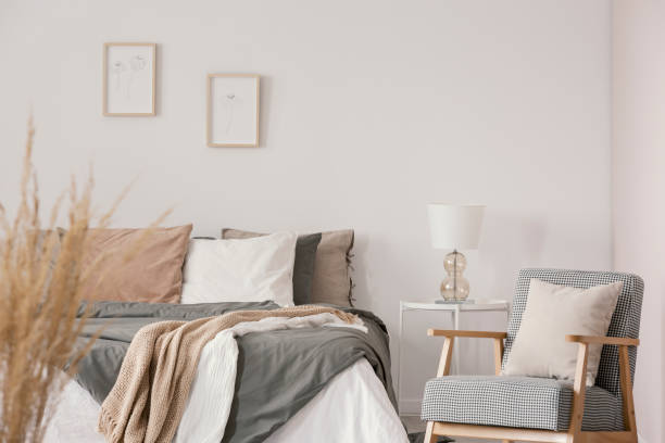 Retro armchair with white pillow next to cozy king size bed with grey bedding in fashionable bedroom interior