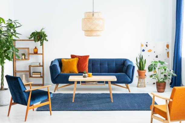Retro armchairs with wooden frame and colorful pillows on a navy blue sofa in a vibrant living room interior with green plants. Real photo. stock photo