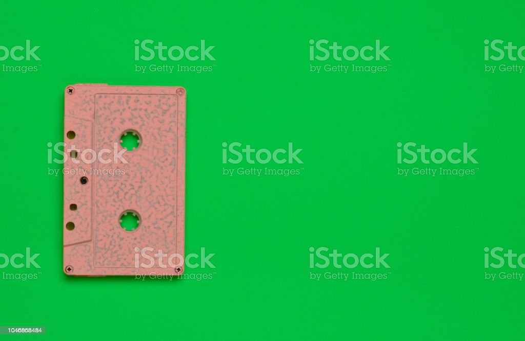 Retro audio cassette on a green bright colored background. Old school technology 80s. Copy space. Top view. – zdjęcie
