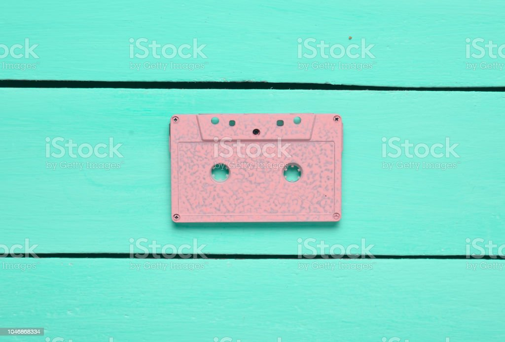 Retro audio cassette on a turquoise wooden background. Trend of minimalism. The concept of obsolete audio technology. Top view. – zdjęcie