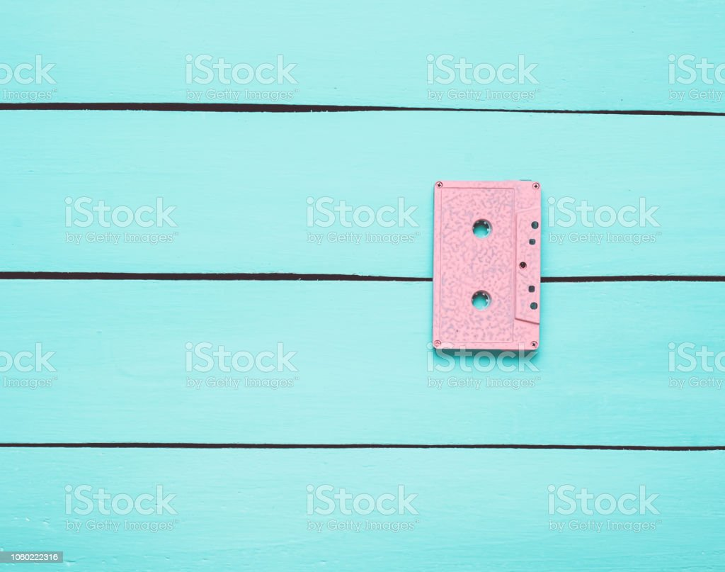 Retro audio cassette on a turquoise wooden background. Trend of minimalism. The concept of obsolete audio technology. Top view – zdjęcie