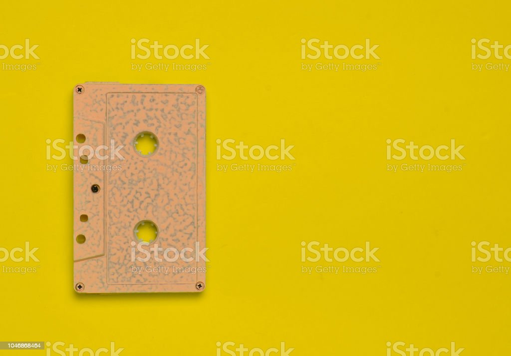 Retro audio cassette on a yellow bright colored background. Old school technology 80s. Copy space. Top view. – zdjęcie