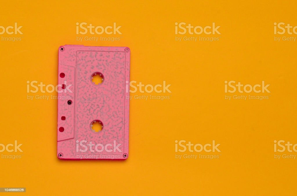 Retro audio cassette on an orange bright colored background. Old school technology 80s. Copy space. Top view. – zdjęcie