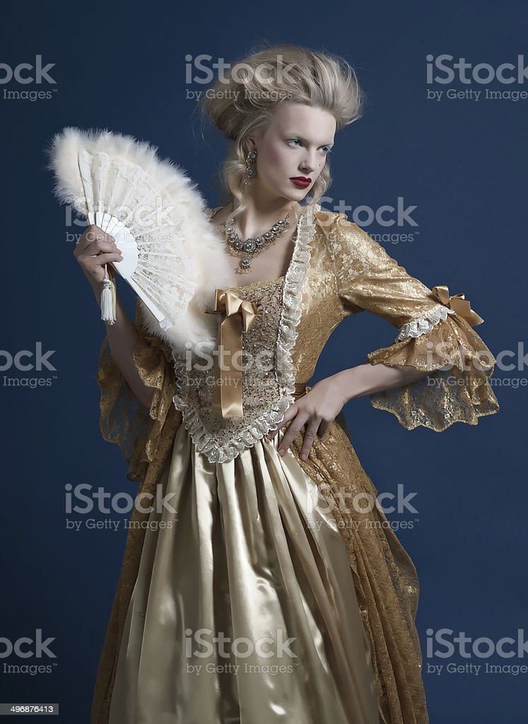 Retro baroque fashion woman wearing gold dress. Holding a fan. royalty-free stock photo