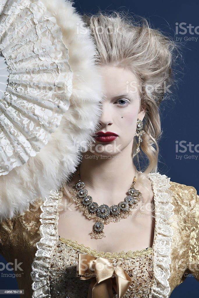 Retro baroque fashion woman wearing gold dress. Holding a fan. stock photo